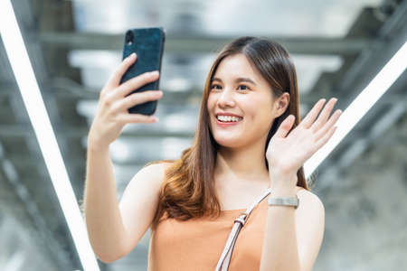 Young Asian woman passenger using smart mobile phone for selfie or video conference to her friend in subway interchange when traveling in big city,enjoy weekend vacation after covid19 Relaxation measures