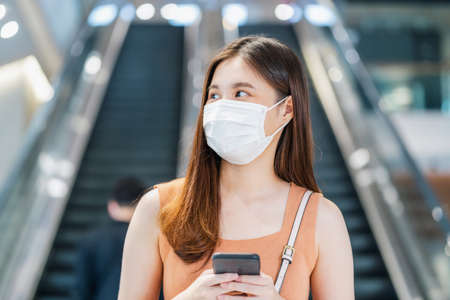 Young Asian woman passenger wearing surgical mask and using smart mobile phone in front of escalator between walk though subway interchange when traveling in big city at Covid19 outbreak, new normal