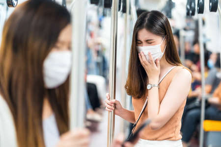 Young Asian woman passenger wearing surgical mask and sneezing in subway train when traveling in big city at Covid19 outbreak, Infection and Pandemic, social distancing and new normal concept