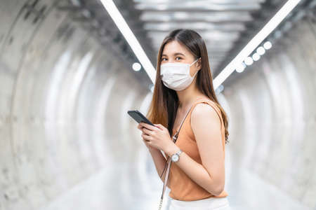 Young Asian woman passenger wearing surgical mask and looking at camera in subway train interchange when traveling in big city at Covid19 outbreak, social distancing and new normal concept 免版税图像