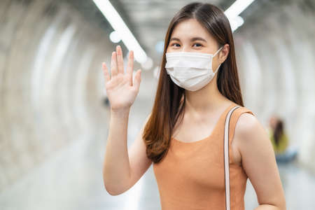 Young Asian woman passenger wearing surgical mask and looking at camera to hello or greeting with her friend in subway interchange when traveling in big city at Covid19 outbreak, new normal concept 免版税图像