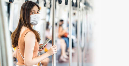 Young Asian woman passenger wearing surgical mask and looking at camera in subway train when traveling in big city at Covid19 outbreak, Infection and Pandemic, social distancing and new normal concept 免版税图像