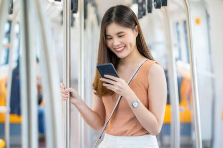 Young Asian woman passenger wearing surgical mask and listening music via smart mobile phone in subway train when traveling in big city at Covid19 outbreak, Infection and Pandemic concept