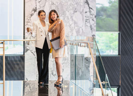 Two asian businesswomen walking and talking during coffee break in modern office or coworking space, coffee break, relaxing and talking after working time, business and people partnership concept