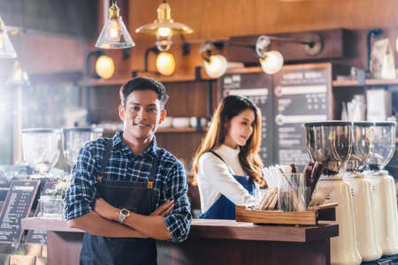 Portrait of Asian Young Small business owner with coffee shop in front of counter bar, entrepreneur and startup, preparing for service to customer in cafe store and restaurant,business partner concept 免版税图像