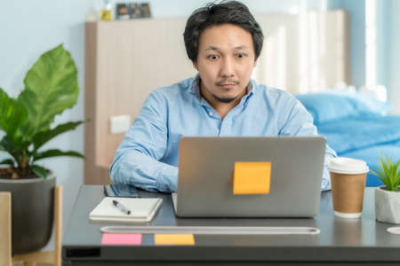 Asian business man using technology laptop and working from home with surprise action in bedroom of house by video conference call,startups and business owner,social distance and new normal concept