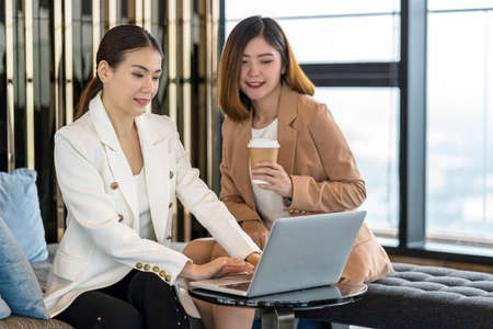 Two asian businesswomen working with the partner business via technology laptop in modern meeting room, office or working space, coffee break, partner and colleague concept