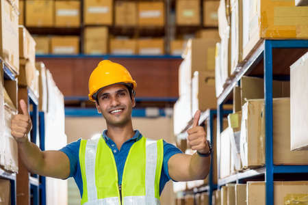 Portrait of Indian warehouse worker man with safety clothes standing with confident and showing thumps up in local workplace with warehouse or factory, success and achievement concept.