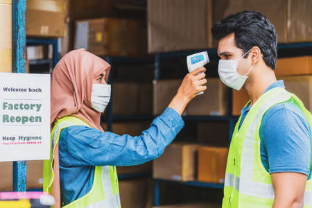 Muslim woman worker uses Medical Digital Infrared Thermometer measure temperature to Indian man worker with safety clothes before start to work after warehouse reopen again, new normal concept