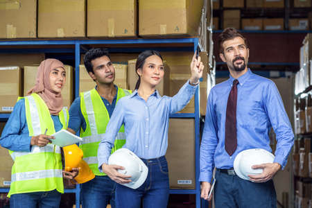 Group of Diversity warehouse worker checking and pointing to product when walking and meeting in local warehouse, muslim, indian, white caucasian and asian people working in export industry concept