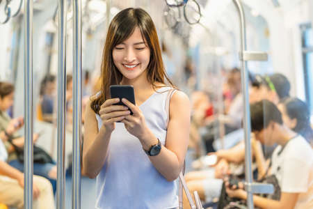 Young Asian woman passenger wearing surgical mask and listening music via smart mobile phone in subway train when traveling in big city at outbreak, Infection and Pandemic concept Reklamní fotografie