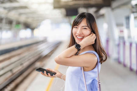 Young Asian woman passenger wearing surgical mask and listening music via smart mobile phone in subway train when traveling in big city at outbreak, Infection and Pandemic concept