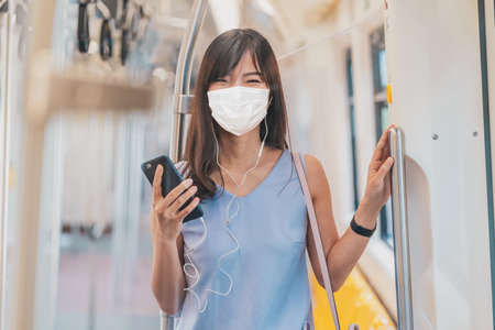 Young Asian woman passenger wearing surgical mask and listening music via smart mobile phone in subway train when traveling in big city at Covid19 outbreak, Infection and Pandemic concept Reklamní fotografie
