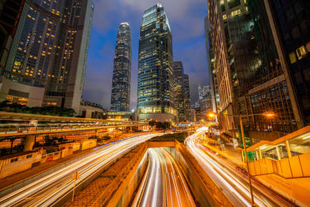Long exposure of Hong Kong Cityscape skyscaper which have light traffic transportation from car or bus on Central Business District around IFC building, transport and energy industrial concept