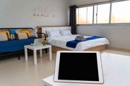 Technology tablet over the Luxury Interior living room, service apartment and Accommodations Concept