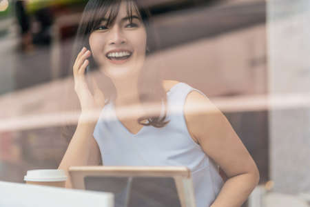 Asian woman using credit card with mobile phone for online shopping in modern coffee shop, technology money wallet and online payment concept, credit card mockup