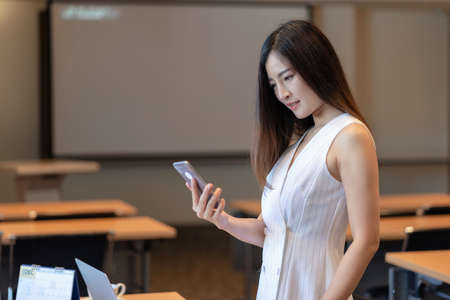 Asian Businesswoman in casual suit working with smart mobile phone and office supplies in modern office or meeting room, Business and worker concept Zdjęcie Seryjne