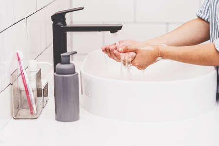 Closeup-up Asian woman hand washing with faucet water in Bathroom at home, Health care of Covid-19 pandemic , cleaning and carefree concept