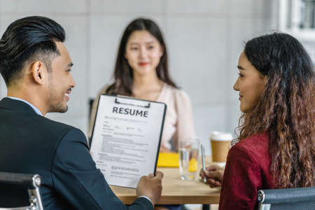 Young Asian woman graduate interviewing with two manager when discuss about her resume with serious motion in meeting room,Business Hiring new member concept