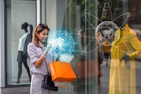Asian woman using the smart mobile phone for check online shopping order is completed via omni channel technology with clothes beside the glassess in store shop with happy action at department center
