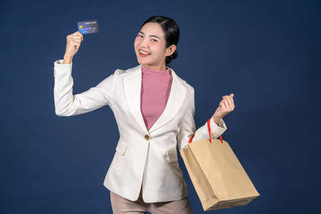 Happy young Asian woman looking credit card and using mobile phone for online shopping on blue color background, cashless payment, black friday and consumerism concept, carrying shopping bags