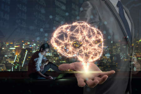 Double exposure of Businessman hand holding the brain base on sparkle over Asian businessman using the smart mobile phone showing the Stock market chart , Artificial Intelligence or AI concept