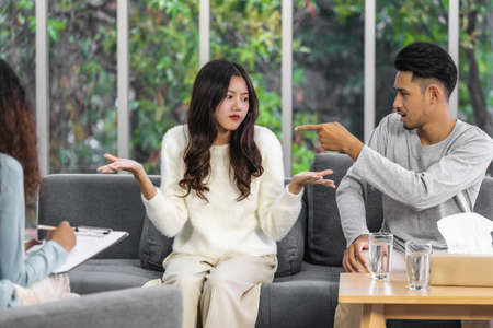 Rear view of coach listening and looking Asian young lovers Arguing about their problem, Psychologist couple and hypnosis concept, deny and argue,life coach and coaching in private indoor home concept