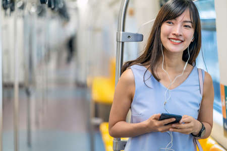 Young Asian woman passenger listening music via smart mobile phone in subway train when traveling in big city,japanese,chinese,Korean lifestyle and daily life, commuter and transportation concept Zdjęcie Seryjne