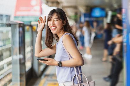 Asian woman at train station platform