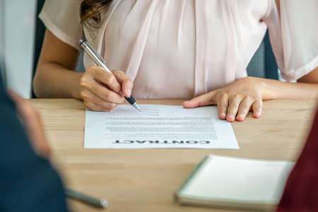 Young Asian woman graduate hand signing the contract after interview