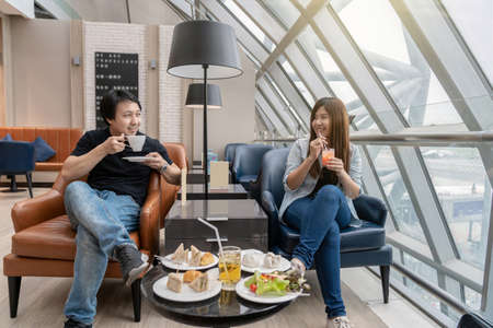Asian couple sitting and eatting inn airport lounge when waiting the flight at modern international airport, travel and transportation concept Zdjęcie Seryjne