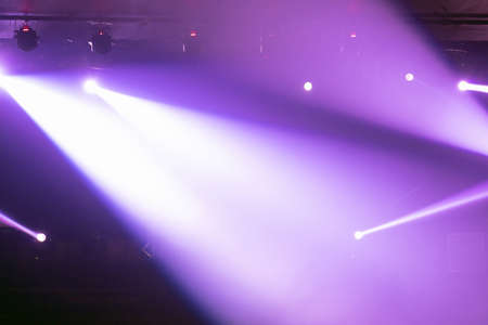 Abstract blurred photo of spotlight on the stage in conference hall or nightclub, silhouette audience or customer in restaurant,seminar and party environment,happy new year and merry christmas concept