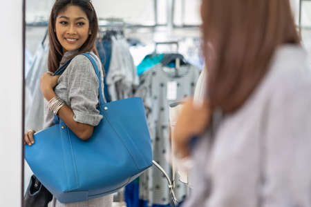Happy Asian woman choosing bag in the store