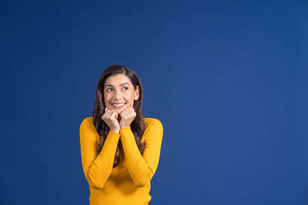 Happy young Asian woman in colorful yellow color casual clothes exciting and looking to copy space on blue color background, lifestyle and leisure, travel and tourist, travel and vacation concept Zdjęcie Seryjne