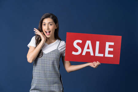 A young woman holding sales banner and looking surprise to sales paper banner for shopping on blue