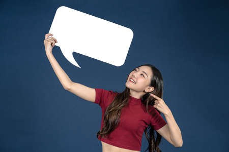 Happy young smiling woman holding copy space empty message bubbles on blue