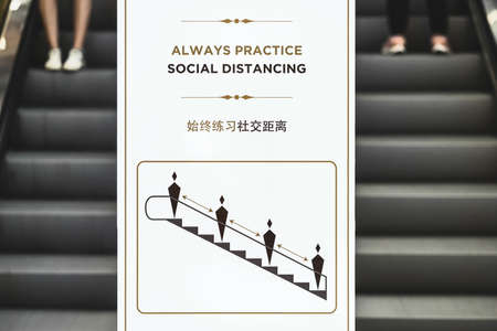 Always Practice and Social Distancing Text with thai and chinese language with the same meaning over the billboard infront of escalator in department store