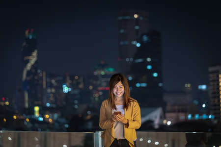 Asian businesswoman using smart mobile phone with smile action in the financial district area at bangkok river side, Thailand, technology with career concept Zdjęcie Seryjne