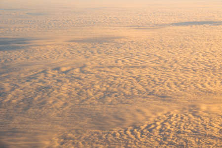 golden cloud over the blue sky Out side above view from airplane side windows when sunrise, landscape cover, advertisement and mockup, transportation and traveler concept Zdjęcie Seryjne