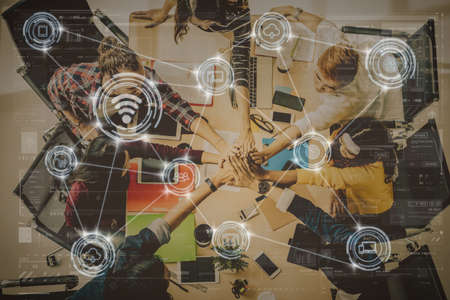 Technology digital virtual screen and Wireless communication connecting over Top view scene of Asian and Multiethnic Business people sitting and Hand coordination for teamwork in the modern workplace