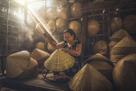 Vietnamese Old woman craftsman making the traditional vietnam hat in the old traditional house in Ap Thoi Phuoc village, Hochiminh city, Vietnam, traditional artist concept Zdjęcie Seryjne