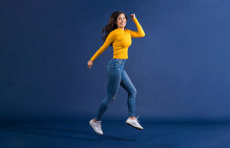Happy young Asian woman showing credit card and using mobile phone for online shopping on blue color background, cashless payment, black friday and consumerism concept, carrying shopping bags Zdjęcie Seryjne - 164540711