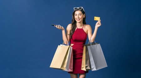 Happy young Asian woman showing credit card and using mobile phone for online shopping on blue color background, cashless payment, black friday and consumerism concept, carrying shopping bags