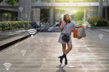 Portrait of Happy Asian woman walking and holding the shopping bag which online shopping via omni channel technology in downtown around shopping center, fashion and multichannel concept