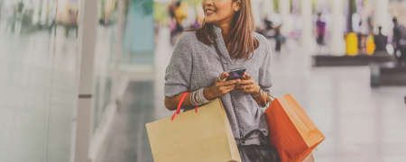 Banner cover of Asian woman using the smart mobile phone for check online shopping order with clothes beside the glassess in store shop at department center,shopaholic and fashion concept Zdjęcie Seryjne