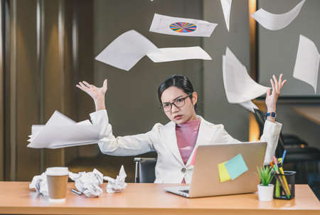Asian businesswoman angry throwing papers over the herself in office when job fail, unsuccessful project, work hard and Overworked and stressed Concept, Zdjęcie Seryjne - 164873576