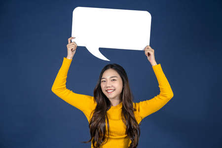 Happy young smiling Asian woman holding copy space empty message bubbles on blue color background, thinking and specking via balloon blank paper, Private opinion for advertisement Concept Zdjęcie Seryjne