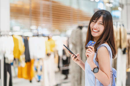 Asian woman using credit card with mobile phone for online shopping in department store over the clothes shop store background, technology money wallet and online payment concept, credit card mockup Zdjęcie Seryjne