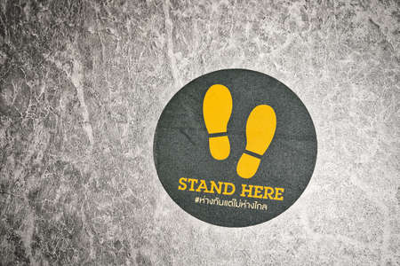 pandemic, new normal Concept, Stand here Text with thai language with the same meaning on the floor in department store