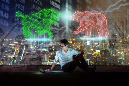 Asian businessman sitting and using the smart mobile phone showing Bull and Bear polygonal shape writing by lines and dots over Stock market exchange and Trading graph on the cityscape background